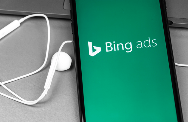 Bing Ads white text on green background on phone screen with ear bud adjacent