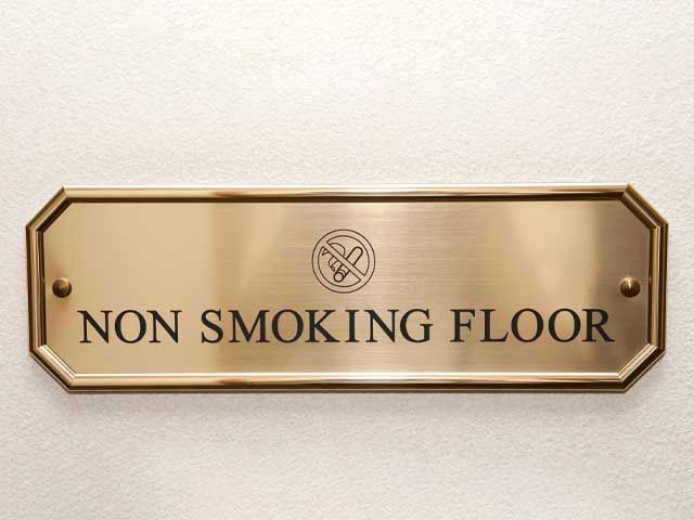No Smoking gold metal lobby sign