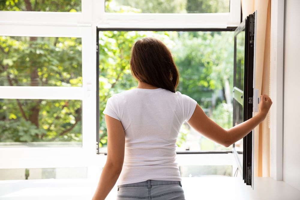 A woman with dark hair opens her window and looks outside.