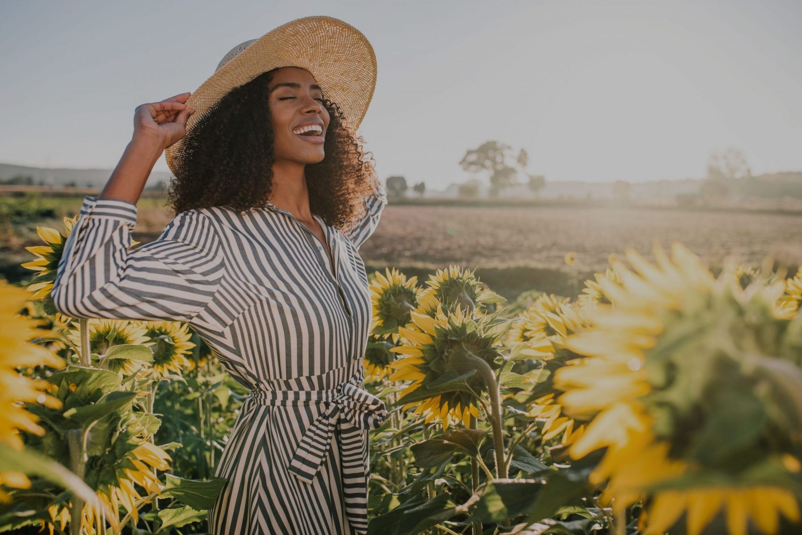 A woman is smiling and laughing while she is in a sunflower field.