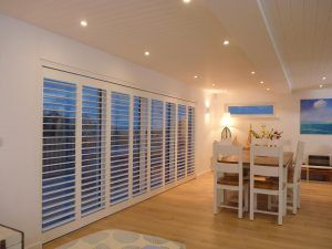 Tracked Plantation Shutters Across Wide Patio Doors In Dining Room