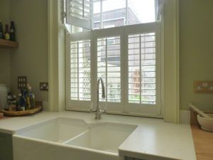 Cream Tier On Tier Shutters Above Sink In Kitchen