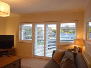 White Louvered Shutters On French Doors And Windows