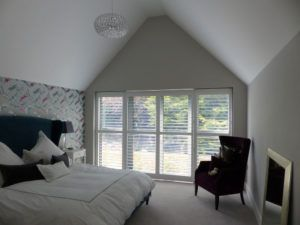 White Shutters Across Large Patio Doors In Bedroom
