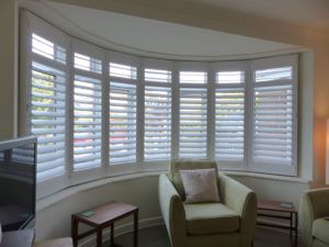 White Louvered Shutters On Large Round Bay Window