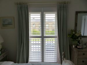White Shutters With Green Curtains On Bedroom Doors