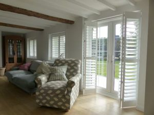 White Bi-Folding Shutters On Patio Doors