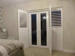 White Shutter Blinds Open Across French Doors
