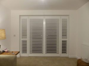 White Wooden Shutters On Living Room Doors