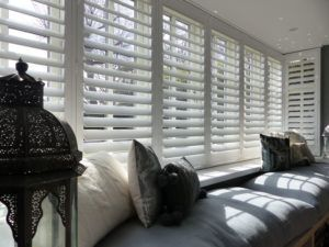White Louvered Shutters In Large Square Bay Window With Cushioned Seat