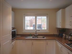 White Louvered Shutters On Kitchen Window