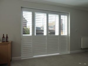White Louvered Shutters With Bottom Louvers Closed On Patio Doors