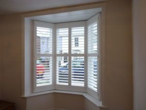 Four Panel Angled Bay Window With White Shutters